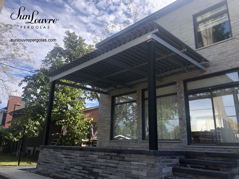 Pergola SunLouvre grise et noire avec toit de lames orientables qui s'ouvrent et se ferment offrant une protection contre le soleil ou la pluie sur la terrasse, modèle Classique - image 2205
